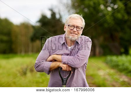 farming, gardening, agriculture and people concept - happy smiling senior man with garden tool at farm