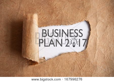 Torn piece of scroll uncovering business plan 2017 with zero figure as a light bulb symbol sketch
