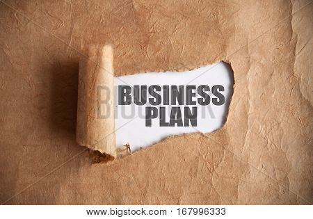 Torn piece of scroll uncovering business plan underneath