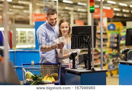 shopping, sale, consumerism and people concept - happy couple buying food at grocery store or supermarket self-service cash register