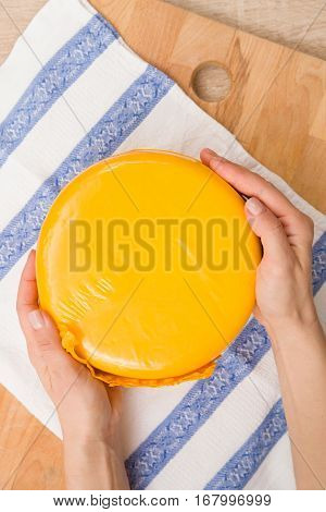 Top view on a head of fresh organic cheese in yellow vacuum package in man's hands. Food concept