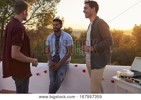 Three male friends talk at a party on a rooftop at sunset