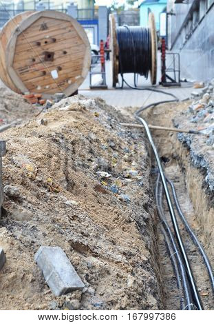 Wooden coil of electric cable and optical fibers in the digging on the street construction site
