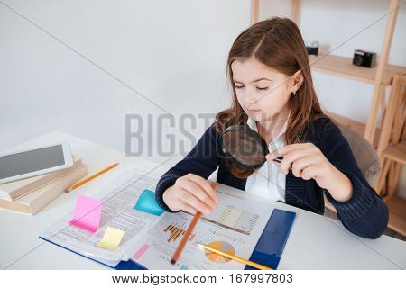 Amusing little girl reading through magnifying glass at the table