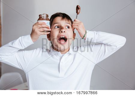 Amusing little boy eating chocolate spread from jar by spoon and shouting