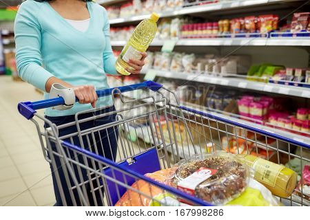 consumerism, food and people concept - woman with shopping cart buying vegetable oil at grocery store or supermarket