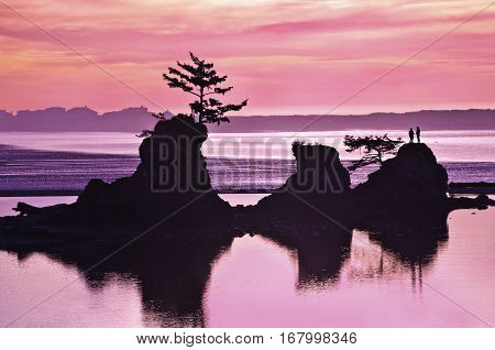 Sunset of ocean beach in Siletz Bay, Oregon with silhouettes of rock and hikers with purple and pink colors