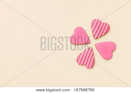 Top view on three little gingerbread cookies in shape of hearts on light yellow background. Flay layout. Love Valentines's day concept