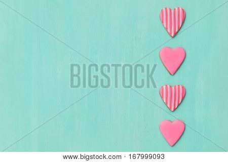 Top view on three little gingerbread cookies in shape of hearts on light blue background. Flay layout. Love Valentines's day concept