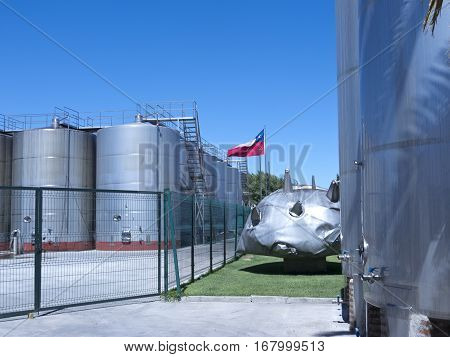 Some wine metallic fermentation tanks. Wine industry in Chile. The broken container is a memory about earthquakes