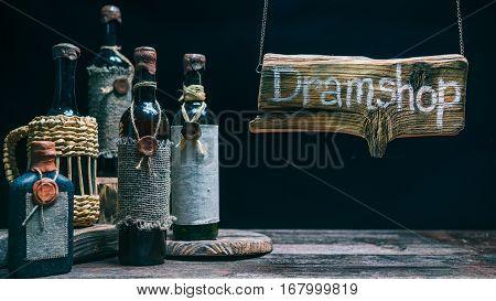Wood sign in light beam above counter in dram shop. Vintage wine bottles. Concept for sign of online or offline dram store