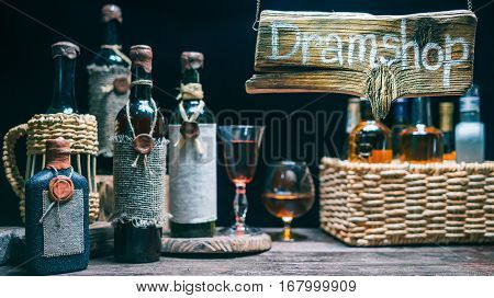Various wine and liquor bottles and wineglasses on the counter in traditional dram shop. Concept for online or offline dram store