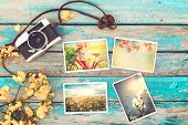 Retro camera and instant paper photo album on wood table with flowers border design - photo of remembrance and nostalgia in spring. vintage style poster