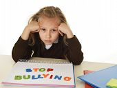 sweet sad and depressed young schoolgirl with stop bullying text on notebook looking helpless and scared as victim of bullying at school in education problem concept isolated white background poster