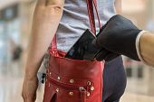 Pickpocket thief is stealing smartphone from red handbag. poster