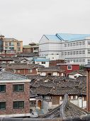 Traditional rooftops of a hanok village in downtown Seoul contrasts with modern skyscrapers in the background. poster