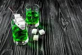 absinthe with sugar cubes and spoon on wooden background close up. poster