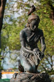 Rusty Statue of Women Pouring Water by Conch Shell with Sparrows Over in Thailand