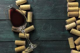 A glass of red wine and wine corks on a dark background. A retro-styled wine tasting invitation, horizontal design template with copy space. Selective focus