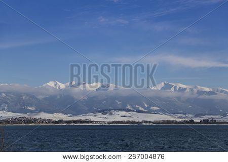 Lake Liptov Sea ( Liptovska Mara) On The Background Of The Snowy Mountain Ridge Of The High Tatras I