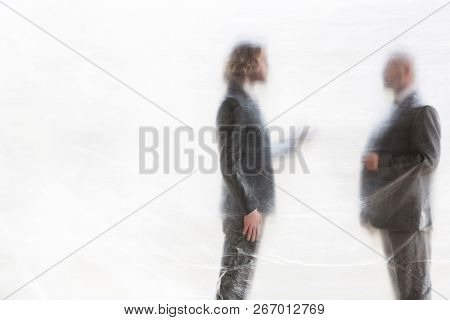 Male business colleagues discussing while standing under plastic at office.creative conceptual photo showing that people become trapped in their jobs and careers that takes up all their time