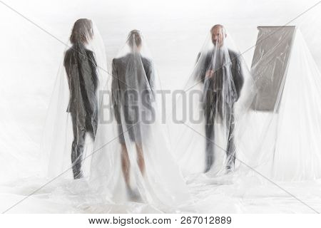Business team covered in plastic standing at office during meeting.creative conceptual photo showing that people become trapped in their jobs and careers that takes up all their time