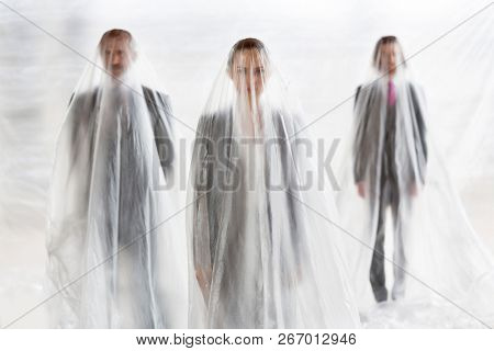 Trapped business people covered in plastic standing at office.creative conceptual photo showing that people become trapped in their jobs and careers that takes up all their time