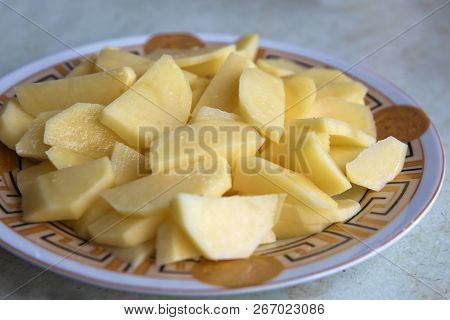 Uncooked Cubical Yellow Potatoes On A Chopping Board. In The Chopped Potato Plate . Sliced, Peeled R