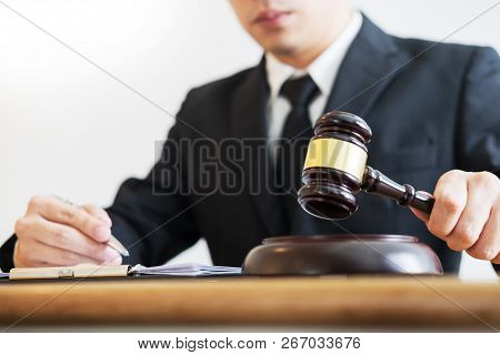 Justice And Law Concept.male Judge Lawyer In A Courtroom Giving Verdict By Hitting Mallet Gavel On S