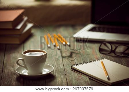 A Cup Of Coffee In The Workplace On A Wooden Table. A Cup Of Coffee In The Workplace On A Wooden Tab