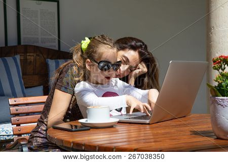 Happy Girl With Sunglasses Touching Laptop Keyboard Next To Mother