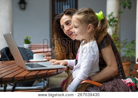Little Girl And Mother Smiling Watching Laptop