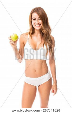 Portrait Of Redhead Woman In Undergarments Holding Apple In Studio