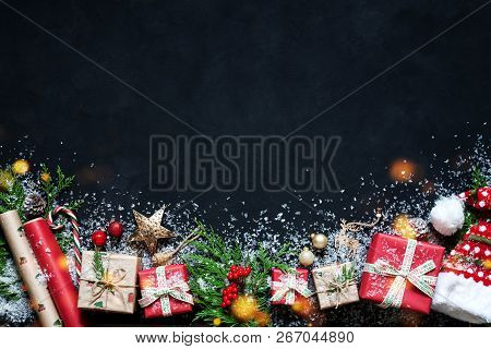 Christmas Composition On A Black Background Christmas Decorations, Boxes, Branches Of Tree, Cap, San