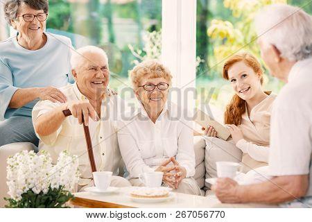 Happy Elderly People Drinking Tea In The Common Room Of Nursing House