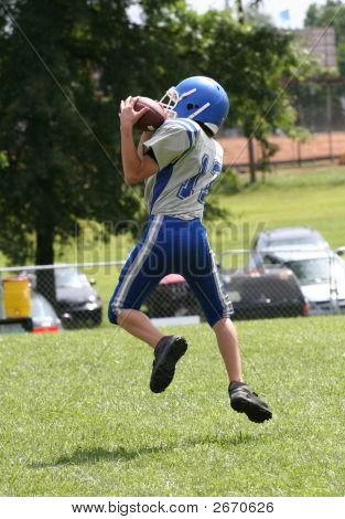 Football Player Catching Football In Air