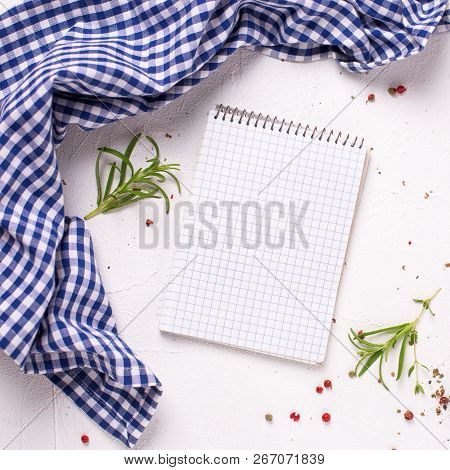 Empty Notebook For Recipes With Fresh Herbs, Spices, Knife And Fork  On Board On Light Textured Back