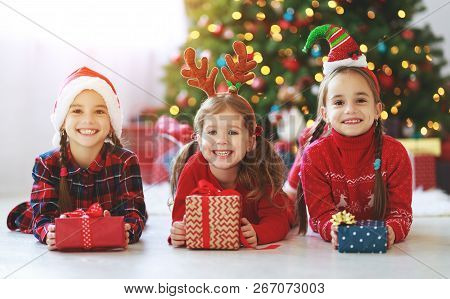 Happy Children Girls With Christmas Gifts Near Christmas Tree In Morning