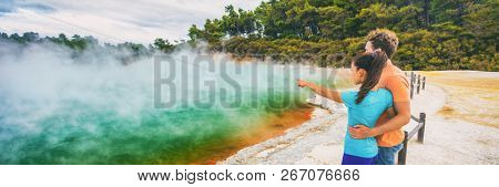 New Zealand travel tourists couple at Champagne pool at Wai-O-Tapu pools Sacred Waters. Tourist attraction in Waiotapu, Rotorua, north island. Panoramic banner, Okataina Volcanic Centre, Taupo.