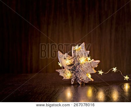 Simple, Natural Christmas Rustic Maple Leaf Ornament Wrapped In Lights On A Dark Wood Background.