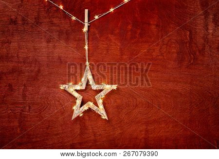 Rustic Christmas Star Decoration Wrapped In Lights On A Beautiful Red Wood Background
