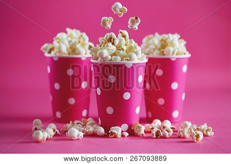 Tasty popcorn falling into cups on pink background. Salty fresh crusty homemade popcorn in pink paper cups.