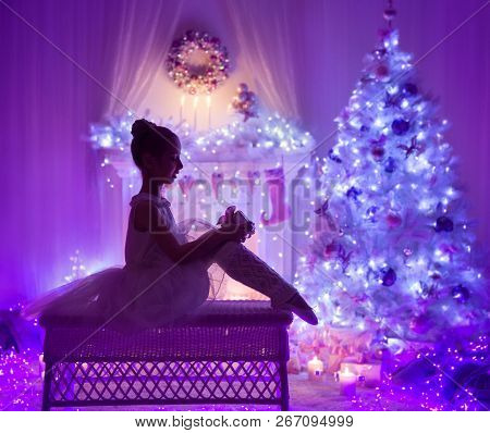 Christmas Child Open Present Gift Box Front Of Xmas Tree Fireplace, Girl Kid In Lighting Night Home