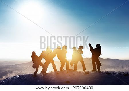 Group Of Happy Friends Skiers And Snowboarders Are Having Fun. Five Silhouettes With Ski And Snowboa