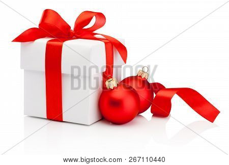 White Gift Box Tied Red Ribbon Bow And Two Christmas Baubles Isolated On White Background