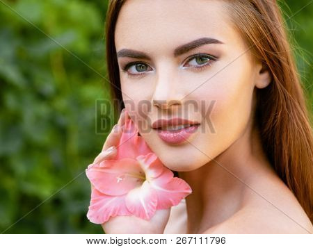 Portrait of beautiful young  woman with clean face. Beautiful face of young adult woman with clean fresh skin - nature. Face of the young beautiful sexy woman outdoors. Beauty face with flower.