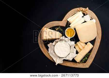 Various Types Of Cheese On Rustic Wooden Table, Goat Cheese, Chevre, Grana Padana, Fig, Blueberry