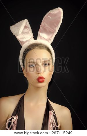 Woman With Duck Face Wearing Rabbit Ears. Sexy Bunny Model. Playboy Girl Posing On Black Background.