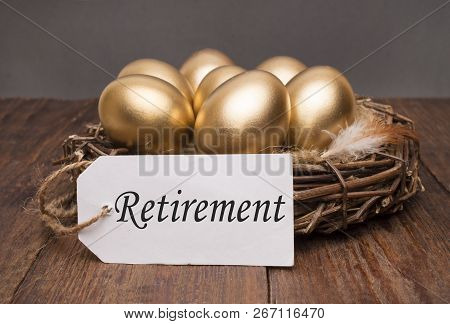 Nest With Golden Eggs With A Tag And A Word Retirement On A Wooden Background. The Concept Of Succes