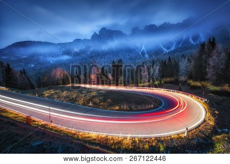 Blurred Car Headlights On Winding Road In Mountains With Low Clouds At Night In Autumn. Spectacular